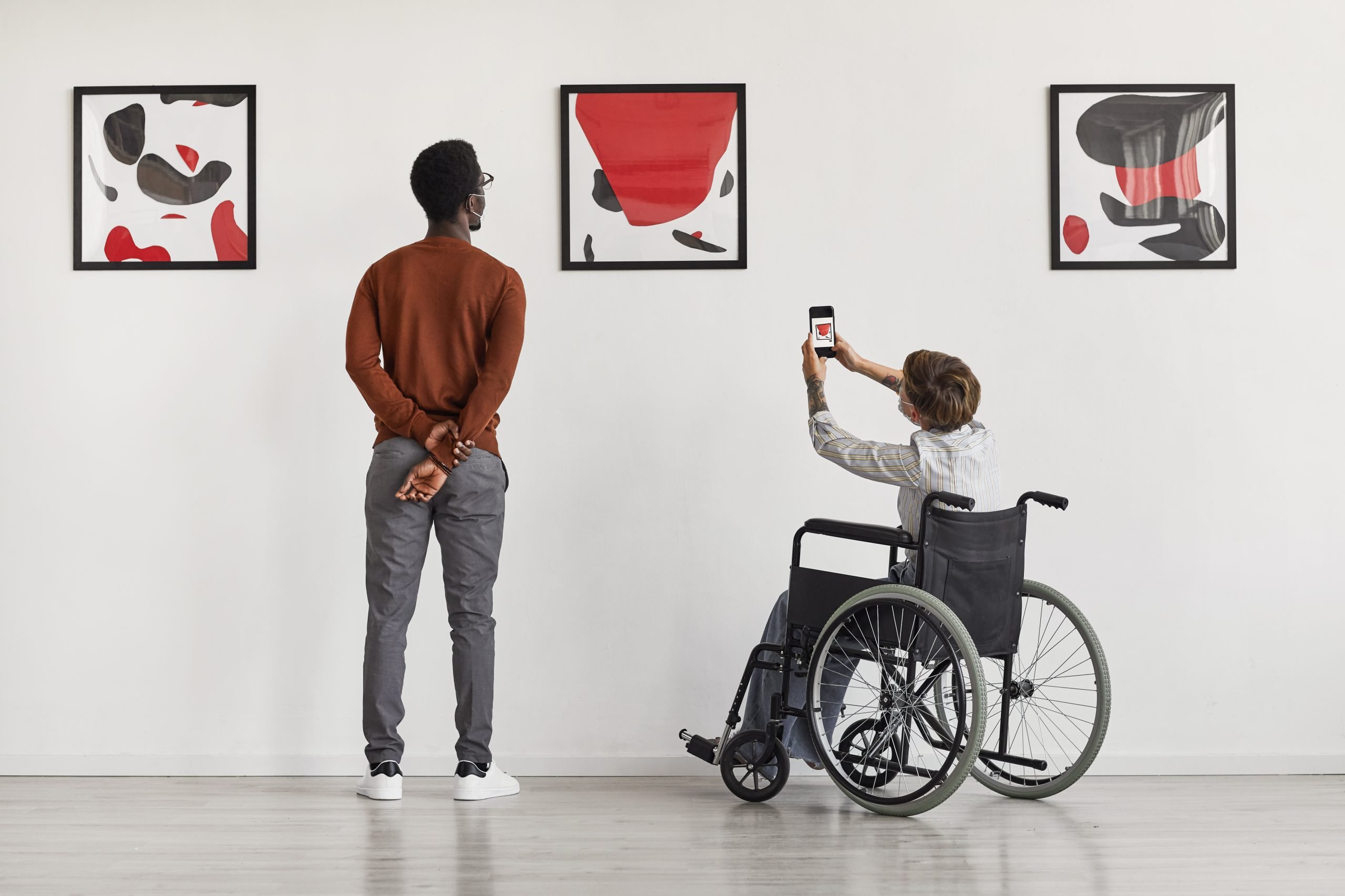 Two individuals, one standing and one in a wheelchair, admire a piece of art in a museum
