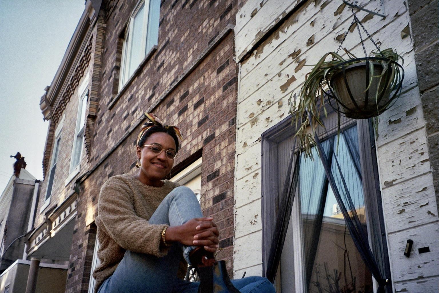 Felicia sitting on the steps near an apartment
