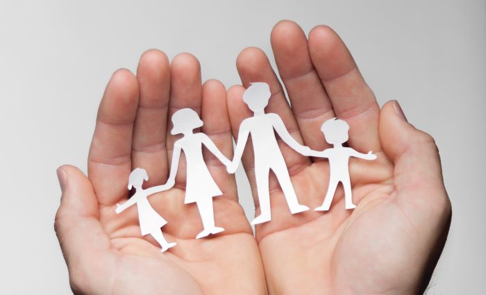 Image of two hands cupped together holding a paper cutout of a family holding hands