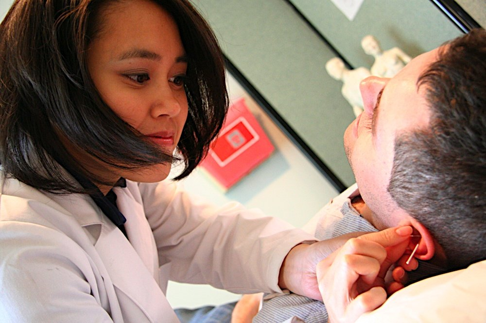 Kim Nguyen giving accupuncture in the ear of a patient.